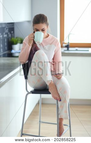 Woman using mobile phone sitting in modern kitchen.
