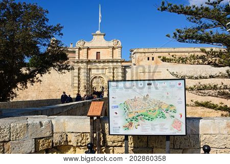 MDINA, MALTA - MARCH 29, 2017 - Footbridge leading to the Town Gate and city centre with a town plan in the foreground Mdina Malta Europe, March 29, 2017.