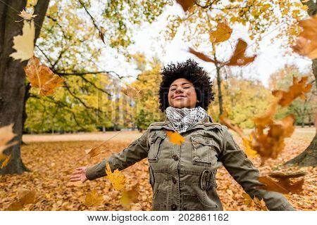 African american woman enjoying autumn season - throwing leaves