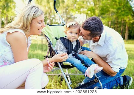 Happy family playing with a baby in a stroller in the park autumn summer.