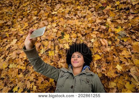 Smiling woman make selfie with yellow leaves