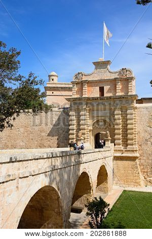MDINA, MALTA - APRIL 1, 2017 - Tourists crossing the footbridge leading to the Town Gate and city centre Mdina Malta Europe, April 1, 2017.