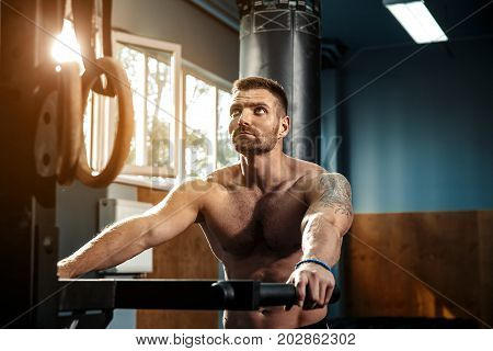 Strong muscular man preparing for workout, push-ups on uneven bars in crossfit gym. Workout lifestyle concept.