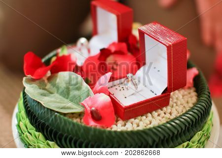 Thai wedding rings in an open box on traditional Thai style garland.engagement ring in Thai wedding ceremony