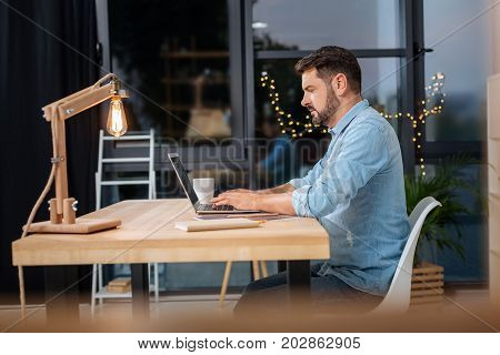 Business project. Smart handsome self employed businessman sitting at the table and using a laptop while working on a business project