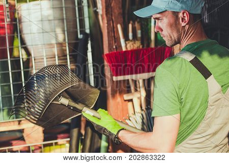 Caucasian Men Buying Right Garden Tools. Brooms and Rakes.