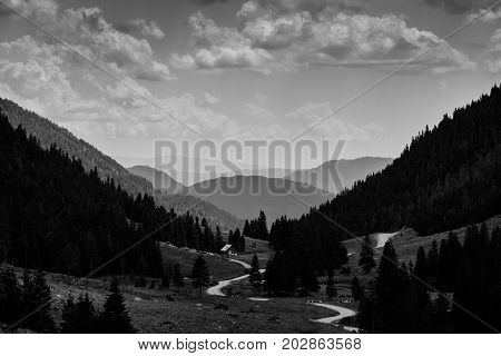 a pathway in the mountains with a hut in B&W