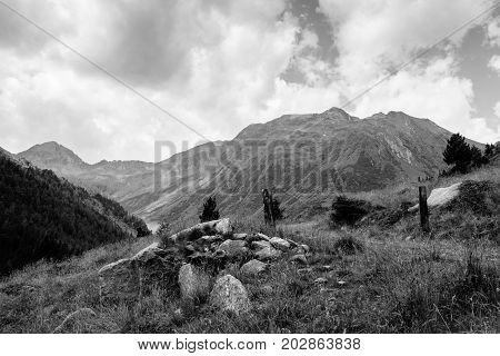 stones in the grass in front of a moutain in B&W