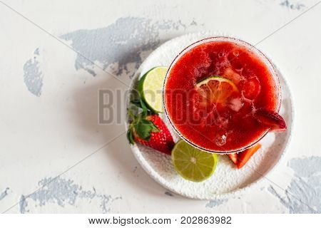 Strawberry daiquiri cocktail with lime and ice cubes. Space for text. Top view