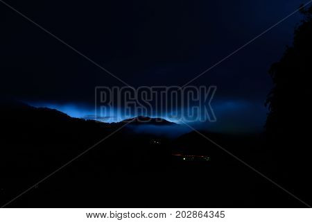 blue glowing sky in the night with a mountain