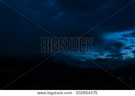 blue glowing sky with clouds in the night