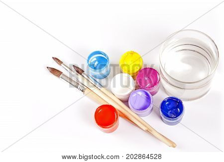 Jars with gouache and paint brushes on a white background