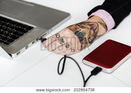 Hand with tattoo connect a external Hdd cable to laptop
