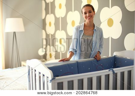 Young woman standing near children's cot. Young mom