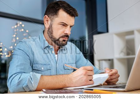 My schedule. Nice serious self employed businessman looking at the laptop screen and taking notes while planning his schedule