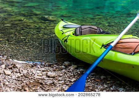 Kayaking on the Lake Concept Photo. Green Sport Kayak on the Rocky Lake Shore. Closeup Photo.