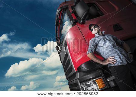 Proud Trucker and His Truck. Caucasian Trucker with Euro Semi Tractor Closeup Photo