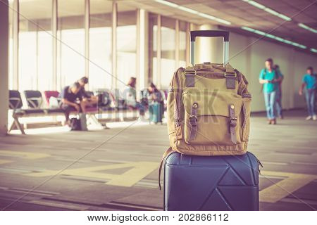 Suitcases and backpack in airport departure terminal with traveler people walking in backgroundHoliday vacation concept Business trip