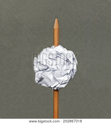 Pencil pierced the ball paper on gray background. with copy space for text.