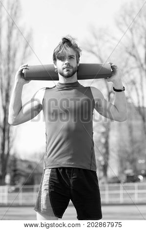man with mat. yoga or fitness mat blue color in hands of man with muscular body and beard exercise in outdoor gym or arena in sportswear energetic handsome guy or sexy bearded macho workout
