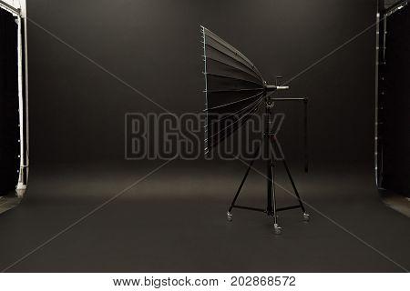 Big studio light standing on black studio backdrop