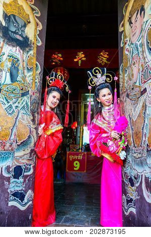 Chachoengsao Thailand - July 14 2013 : Beautiful women with traditional chinese dress at Chinese shrine door with painting of ancient soldier in Thailand.
