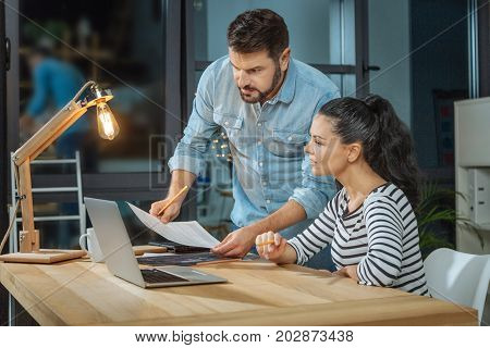 Business partners. Nice pleasant smart woman sitting at the desk and looking at the document while working together with her partner