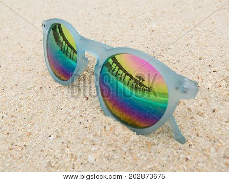 Fashion blue frame sunglasses on sandy sea beach with mirror lenses. Sea beach reflection on black fashion sunglasses. Summer holiday relax background with copy space.