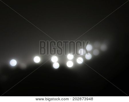 Abstract lights in the fog. Ray of bright white light from a street lamp in the fog. black and white