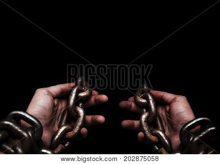 Victim Slave Prisoner male hands tied by big metal chain by him self. People have no freedom concept image.
