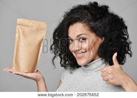 Smiling woman showing craft paper pouch bag with copy space and gesturing thumb up, closeup portrait over grey background.