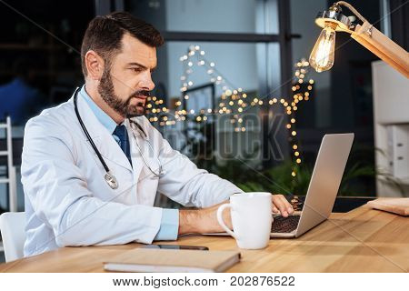 Medical documentation. Intelligent experienced male practitioner sitting at the desk and typing while working with medical documentation