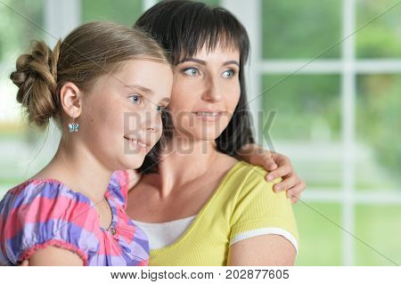 close up portrait of mother and daughter hugging together