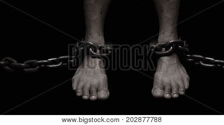 Victim Slave Prisoner male foor tied by big metal chain. People have no freedom concept image.