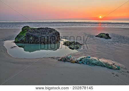 The beach of Ambleteuse at sunset with colorful stones and a fishing net in the foreground, Cote d'Opale, Pas de Calais, Hauts de France