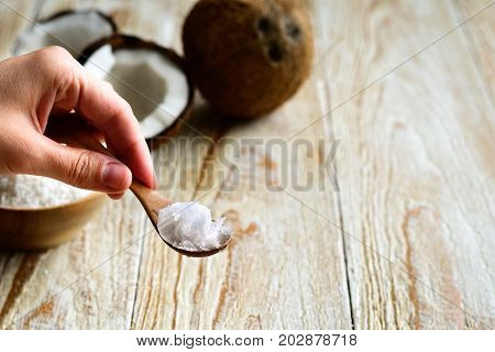 Hand holding spoon with coconut oil. Coconut on background