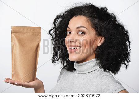 Smiling woman showing craft paper pouch bag with copy space, closeup portrait over grey background.
