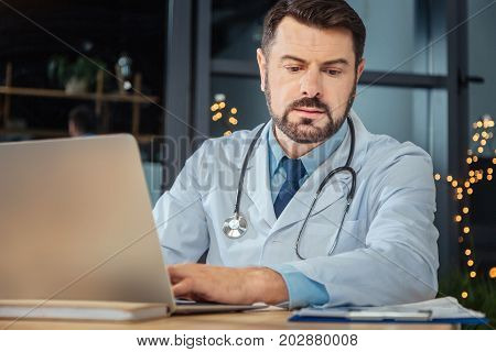 Scientific research. Serious hard working male scientist sitting at the table and using a laptop while doing a scientific research