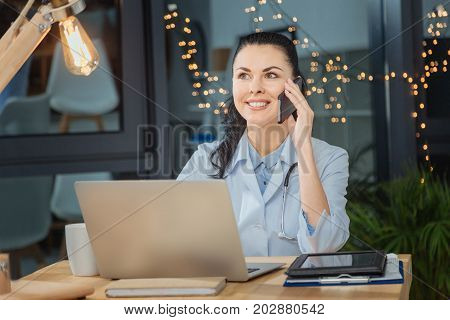 Good mood. Delighted positive nice woman listening to her interlocutor and smiling while being in a good mood