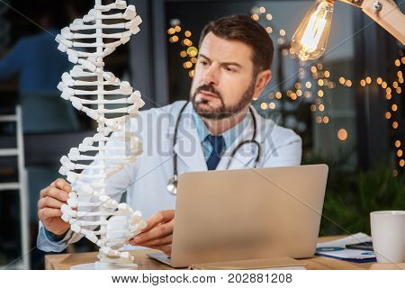 Genome studies. Selective focus of a DNA model standing on the table while being studied by a nice professional male scientist