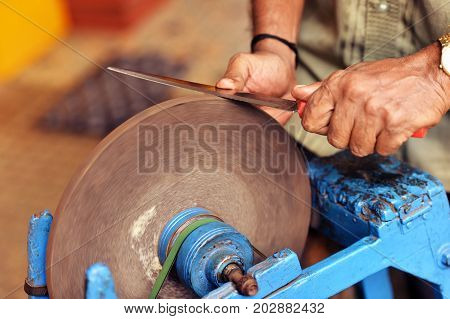 Man grinding knife on grinding wheel disk poster