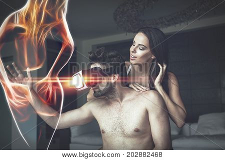 Couple playing with VR glasses at home virtual reality man touching fiery virtual woman in cyberspace cybersex in threesome