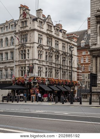LONDON UK - 29 AUGUST 2017: Tourists and office workers outside the Red Lion a traditional English pub on Parliament Street opposite Downing Street in the heart of London's Whitehall.