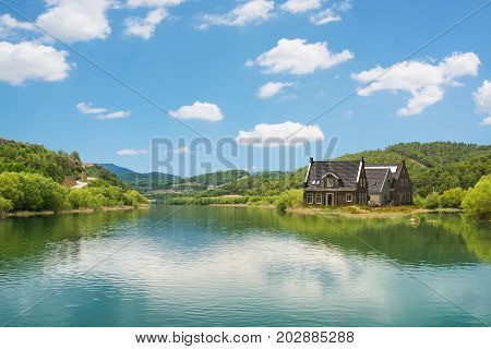 The lakeside house and fresh green nature with blue sky.