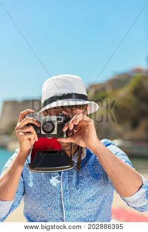 Hipster man photographer taking photo with retro camera.