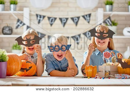 Cute little children with carving pumpkin. Happy family preparing for Halloween. Funny kids at home.