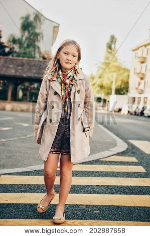 Outdoor fashion portrait of 8-9 year old hipster girl wearing stylish trench coat