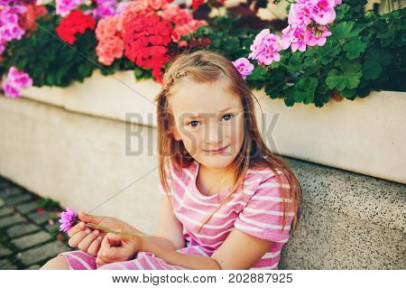 Candid portrait of adorable little 6-7 year old girl holding pink chrysanthemum flower
