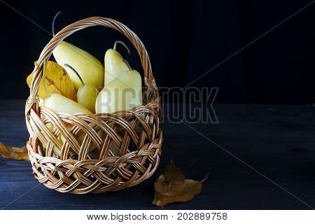 fresh pears in a wicker basket with autumn leaves on a dark wooden background copy space