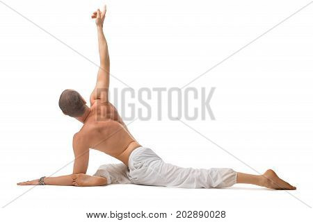 Mature shirtless muscular man wearing wide trousers doing yoga isolated on white